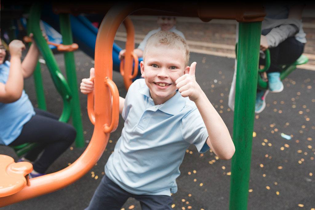 Boy gives thumbs up on Valentine Boys & Girls Club playground.